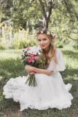 atraktivní mladá nevěsta drží svatební kytice a usmívá se na kameru v parku