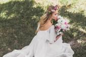 Fotografie Vogelperspektive Blick auf schöne junge Braut im Hochzeitskleid holding Blumenstrauß und wegschauen im park