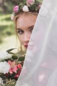 Fotografie krásná mladá blondýnka nevěsta v závoji drží kytici květin a při pohledu na fotoaparát