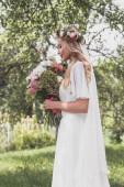 Fotografie Seitenansicht des lächelnden jungen Braut hält Hochzeitsstrauß im park