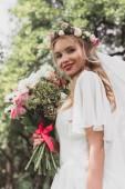 Fényképek alacsony, szög, kilátás gyönyörű fiatal menyasszony, esküvői csokor gazdaság, és mosolyogva kültéri kamera