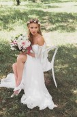 Fotografie high angle view of beautiful tender young bride holding wedding bouquet and sitting on chair outdoors