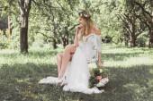 Fotografie zamyšlený mladá blonde nevěsta drží svatební kytice a sedí na židli venku