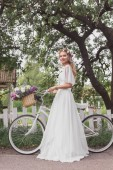 beautiful bride in floral wreath and wedding dress standing with bicycle and smiling at camera