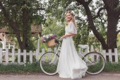 young bride in floral wreath and wedding dress standing with bicycle and smiling at camera