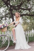 Photo young blonde bride in wedding dress and floral wreath riding bicycle and smiling at camera
