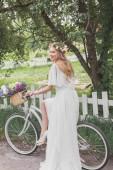 Fotografie krásná usměvavá mladá nevěsta ve svatebních šatech jízda kole