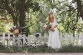 Fotografia bella giovane sposa con bouquet da sposa e biciclette in piedi vicino al recinto e distogliere lo sguardo