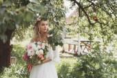 Fotografie beautiful pensive bride holding wedding bouquet and looking away in garden