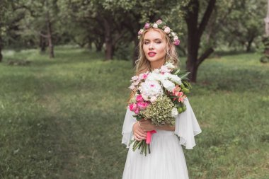 beautiful young blonde bride holding wedding bouquet and looking at camera in park