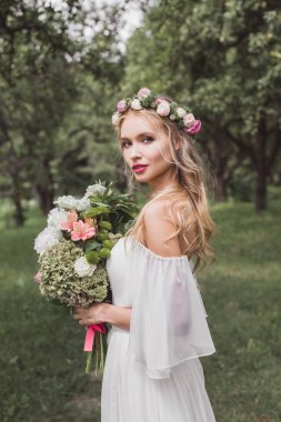 tender young bride in floral wreath and wedding dress holding bouquet of flowers and looking at camera outdoors