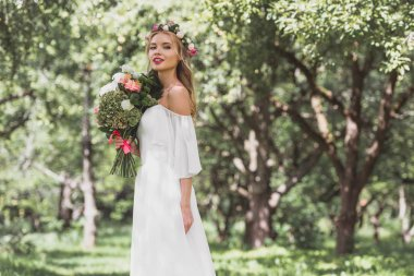 beautiful smiling young bride in floral wreath holding bouquet of flowers and looking at camera