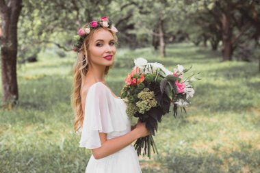 happy bride in wedding dress and floral wreath holding bouquet of flowers and smiling at camera outdoors