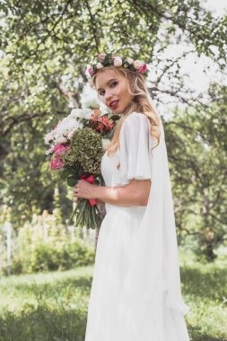 low angle view of beautiful young bride holding bouquet of flowers and smiling at camera