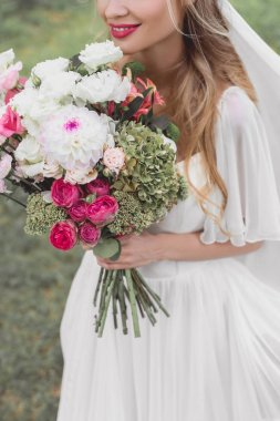cropped shot of smiling young bride holding bouquet of flowers outdoors