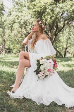 beautiful thoughtful young bride holding wedding bouquet and sitting on chair in park