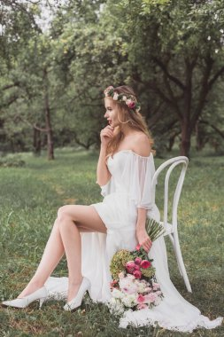 beautiful pensive young bride holding wedding bouquet and sitting on chair outdoors