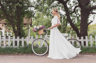 side view of young bride in floral wreath and wedding dress walking with bicycle and looking away