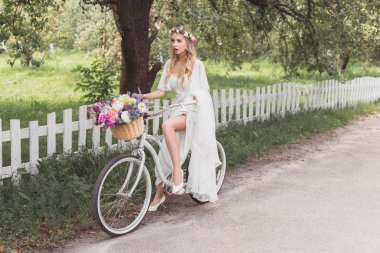 beautiful shocked bride in wedding dress riding bicycle and looking away
