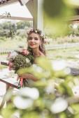 Selektivní fokus krásná mladá nevěsta v květinový věnec drží svatební kytice a usmívá se na kameru
