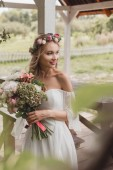 beautiful smiling young bride in floral wreath holding wedding bouquet and looking away