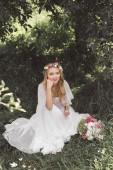 vysoký úhel pohled krásná usměvavá mladá nevěsta sedí na trávě a drží sklenku šampaňského