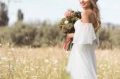 Fotografie oříznutý snímek s úsměvem mladá nevěsta v bílých šatech venku drží svatební kytice
