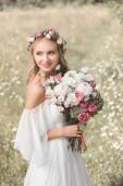 krásná usměvavá blondýnka nevěsta ve svatebních šatech drží krásnou kytici květin venku