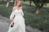 Fotografie high angle view of upset young bride in wedding dress holding bottle of wine and walking in park