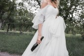 cropped shot of young bride in wedding dress holding bottle of wine and walking in park