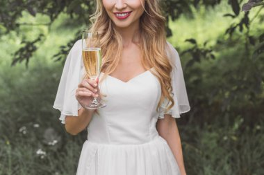 cropped shot of smiling young blonde bride holding glass of wine outdoors