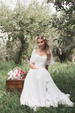 beautiful young bride sitting on vintage chest and looking at camera