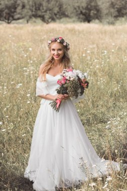 high angle view of beautiful young bride holding bouquet and smiling at camera while standing on blooming field