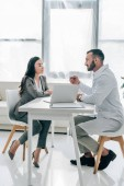 Fotografie side view of patient and doctor talking in clinic with laptop on table