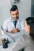 Fotografie Veselý doktor směřující na formuláři pojistného nároku pacienta v klinice