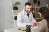 Fotografie pacient podepisování formuláře pojistné události v klinice, usmívající se doktor držení tužky
