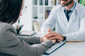 cropped image of patient and smiling doctor holding hands above insurance claim form in clinic