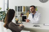 Photo smiling doctor pointing on tablet with blank screen to patient in clinic