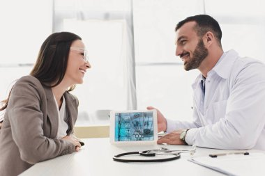 smiling doctor showing patient tablet with medical app in clinic