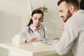 klient a lékař počítání finance na kalkulačce pro zdravotní pojištění v kanceláři
