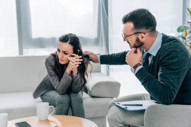 psychologist touching shoulder of crying patient in doctors office