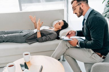 female patient lying on sofa and talking with psychologist in office