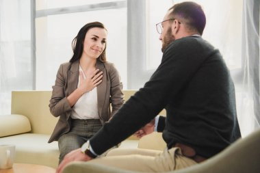 happy patient touching chest in psychologist office
