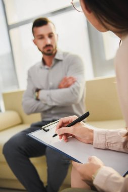 selective focus of patient and psychiatrist writing in clipboard in office