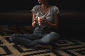 Fotografie cropped view of sad woman with coffee cup sitting on floor at home