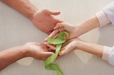 partial view of male and female hands with green ribbon - mental health day