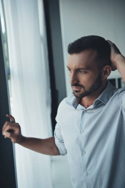 thoughtful lonely man standing at window at home