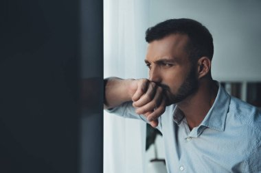 upset pensive man looking at window at home