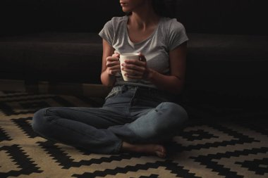 cropped view of sad woman with coffee cup sitting on floor at home