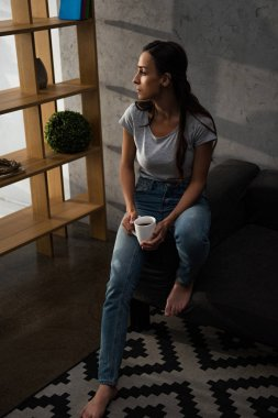 upset woman with cup of coffee sitting on sofa